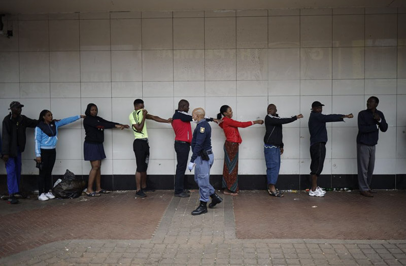 Fuente: A member of the South African Police Service (SAPS) enforces social distancing of shoppers outside a supermarket in Yeoville, Johannesburg, on March 28. Photographer: Marco Longari/AFP via Getty Images