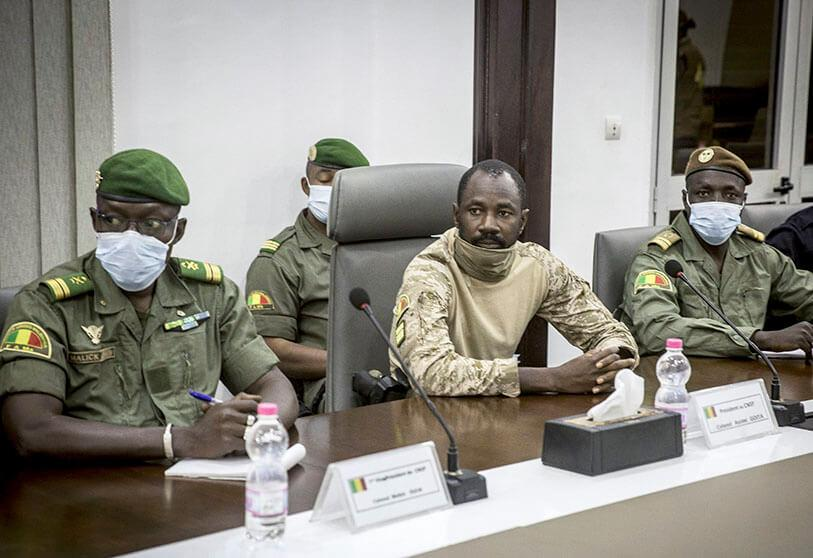 Colonel Assimi Goita, centre, who has declared himself leader of the National Committee for the Salvation of the People, is accompanied by group member Malick Diaw, left, as they meet with a high-level delegation from the West African regional bloc known as ECOWAS, at the Ministry of Defence in Bamako, Mali, on Saturday 22 August 2020