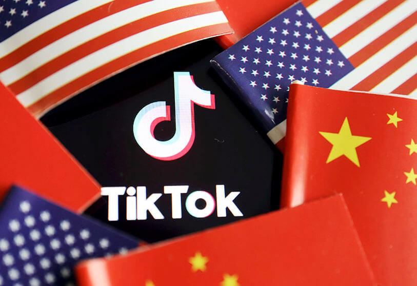 The Chinese and American flags are seen near the TikTok logo