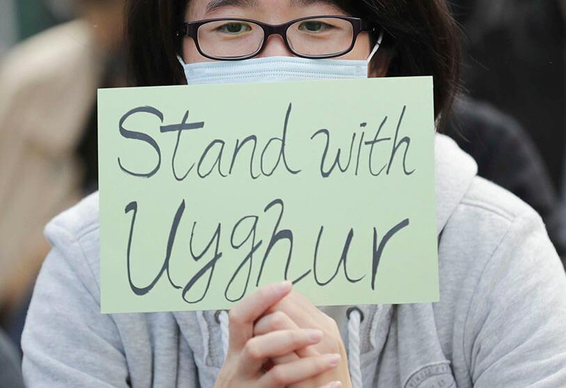 A protester holds a poster during a demonstration to show his support for Uighurs and their struggle for human rights in Hong Kong on 22 December 2019