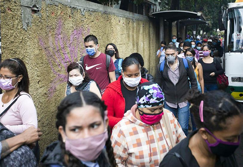Pedestrians and travelers wearing face masks amidst the spread of the new coronavirus walk on a sidewalk where buses stop in Caracas, Venezuela, on Monday, June 1, 2020