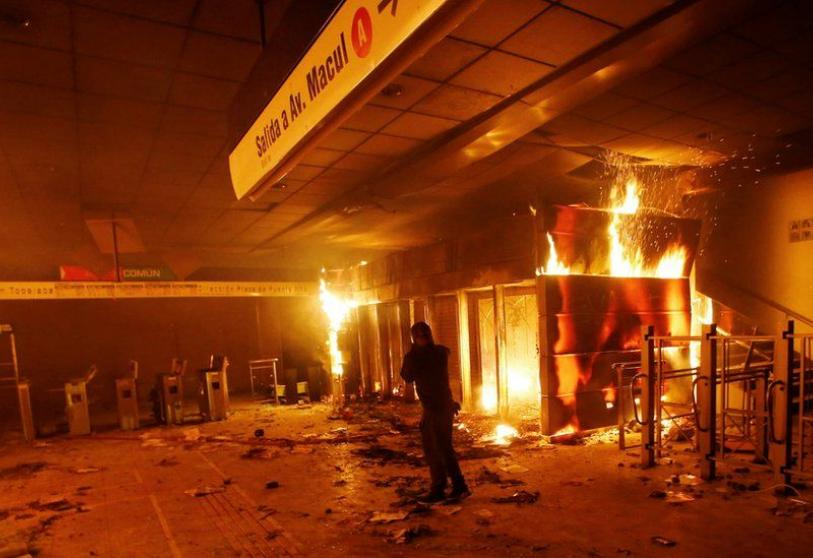 A subway ticket office is seen on fire during a protest against the increase in the subway ticket prices in Santiago, Chile, October 19, 2019