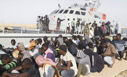 Archival photograph of rescued migrants sitting next to a Coast Guard boat in the city of Khoms, about 120 kilometers (75 miles) east of Tripoli, Libya