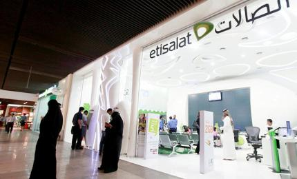 Customers use their mobile phones outside an Etisalat store in a shopping centre in Dubai