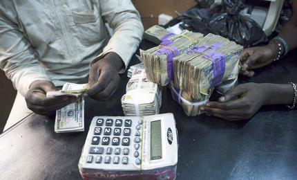 A trader exchanges dollars with naira in a currency exchange shop in Lagos