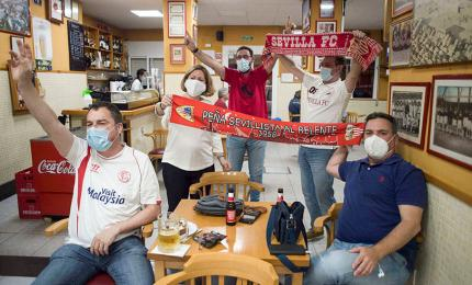 Sevilla FC fans sit in a bar while watching a live broadcast of the Spanish League football match between Sevilla FC and Real Betis played behind closed doors in Seville on June 11, 2020