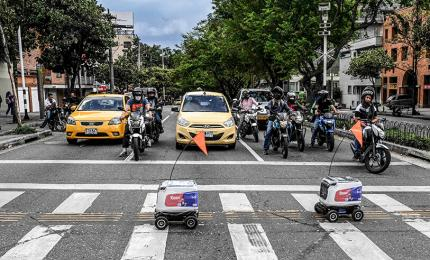 Two delivery robots cross a street in Medellin, Colombia, on April 22, 2020