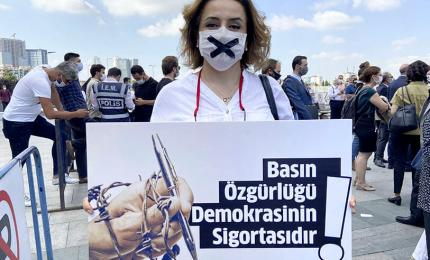 "A woman holds a poster saying ""Press Freedom is the Guarantee of Democracy"" in front of a court in Istanbul on Wednesday, June 24, 2020"